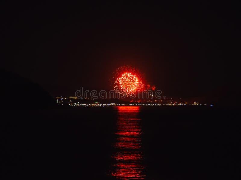 Ljusa röda fyrverkerifyrverkerier över floden royaltyfria bilder