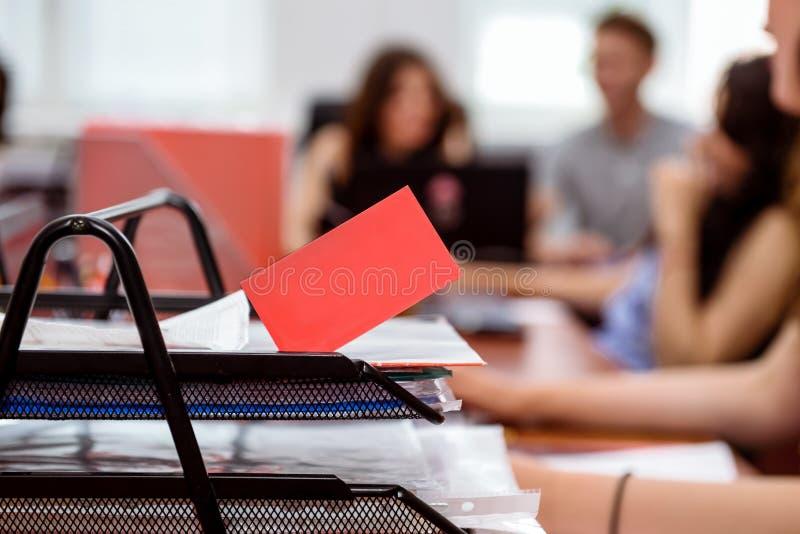 Ljusa röda tomma affärskort på bakgrund av det funktionsdugliga laget, fritt utrymme för text och logo Selektivt fokusera royaltyfria bilder