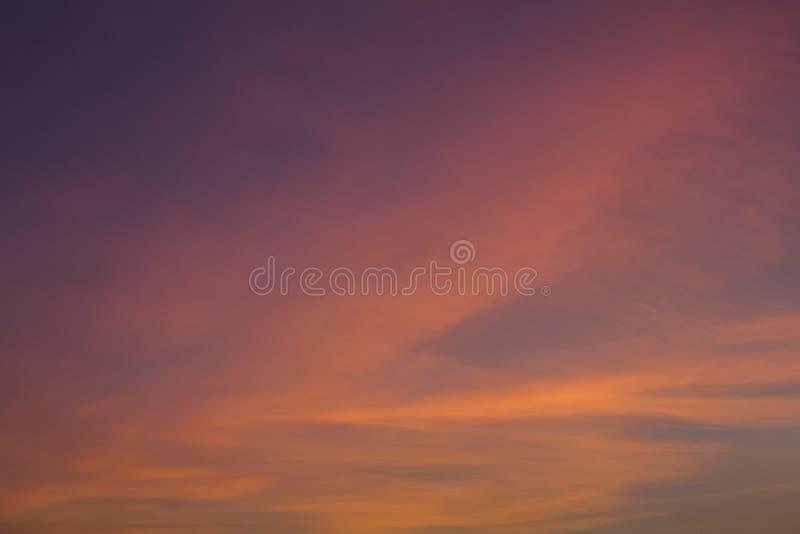Ljusa rosa och gula moln i ett mörkt - blå purpurfärgad solnedgånghimmel arkivfoton