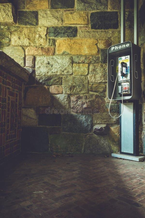 Ljusa sken på ett gammalt telefonbås i hörnet av byggnad smyckade igenom med dekorativa tegelplattor i tappninginställning arkivbilder