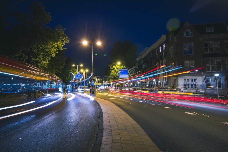 Ljusa slingor av bussar och trafik i Amsterdam, Nederländerna fotografering för bildbyråer
