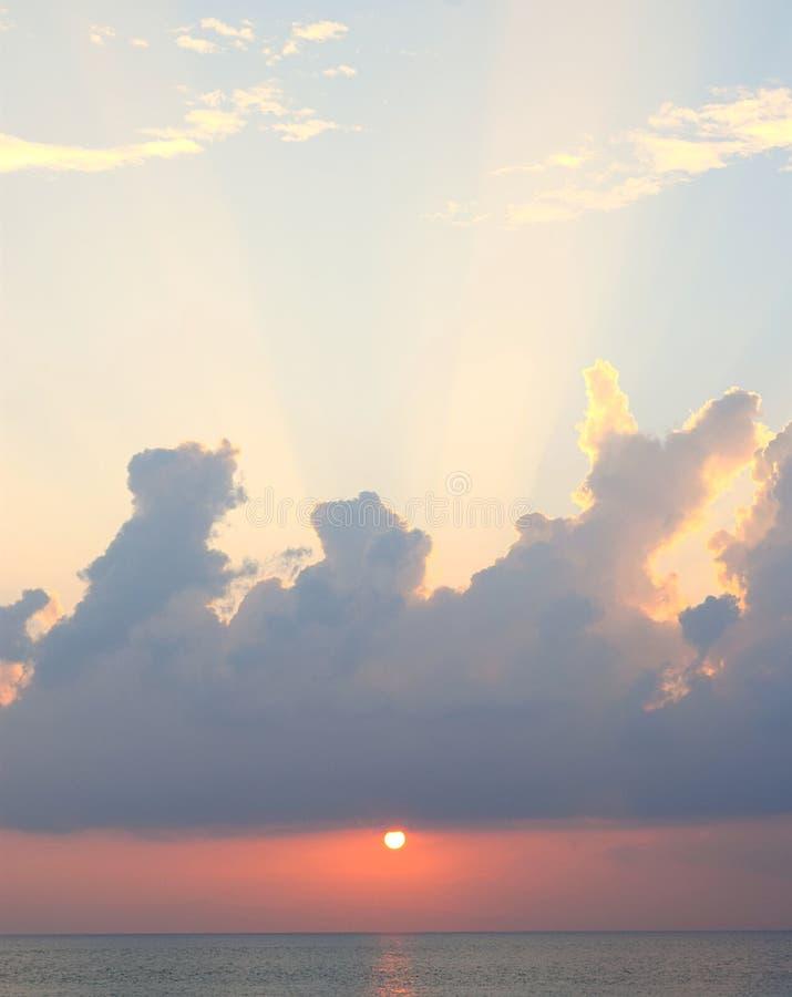 Ljusa solstrålar som kommer till och med moln i blå himmel med den guld- solinställningen över havet royaltyfri bild