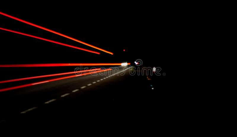 Ljusa spår på en väg på natten royaltyfria foton