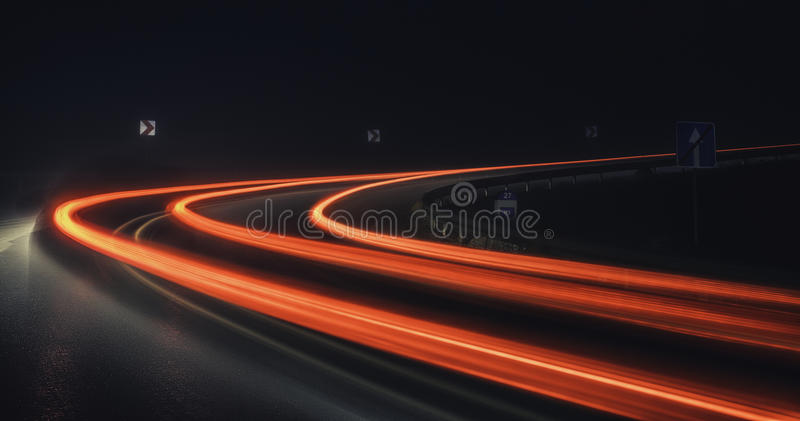 Ljusa spår på vägen på natten arkivfoto