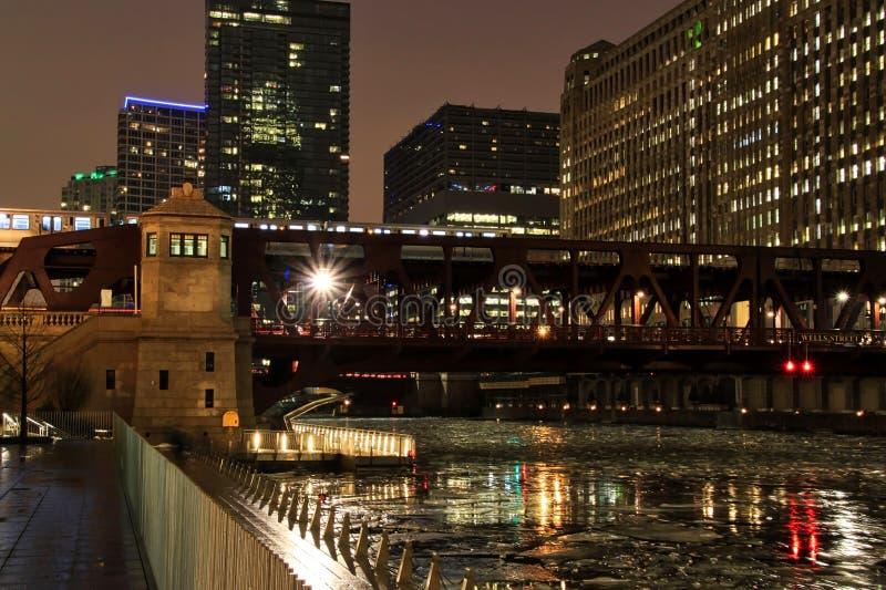 Ljusa strålar fördjupa av av illmuninated ljus från den Chicago bron, som el-drevet rusar förbi arkivbilder