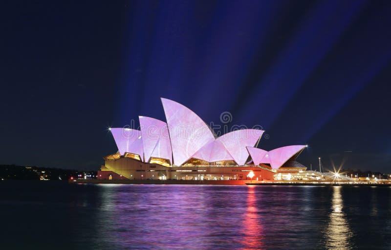 Ljusa strålar projekterar mjuka pastellfärger på Sydney Opera House arkivbild