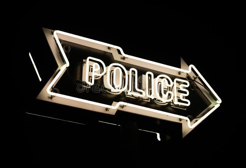 Ljusa vita punkter för neontecken in mot polisstationmörkernatt fotografering för bildbyråer