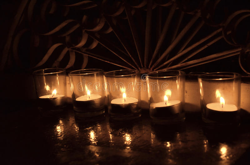 5 ljusa votive stearinljus för te i klar glass ironwork bakom arkivfoton