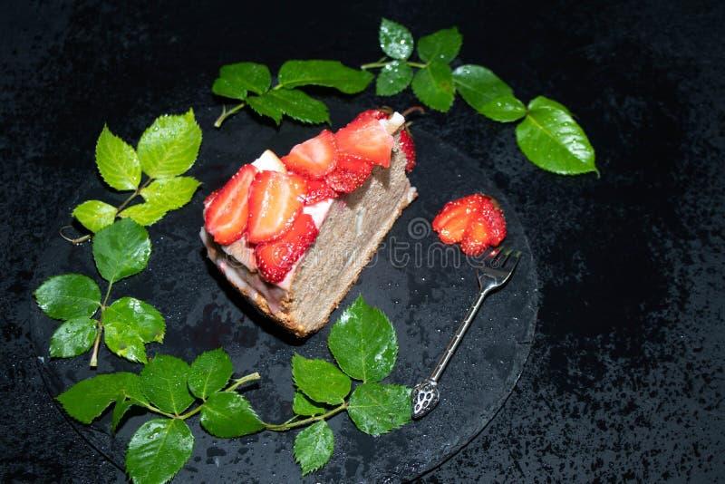Ljusbrun kaka med gräddfil som dekoreras med jordgubbar, nytt bär på ett magasin, med blåa ljus i bakgrunden, royaltyfria foton