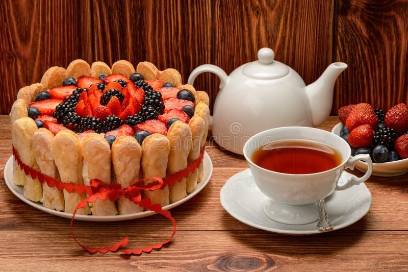 Ljusbrun kaka med jordgubbar, blåbär och björnbär och koppotte på brun träbakgrund arkivbild