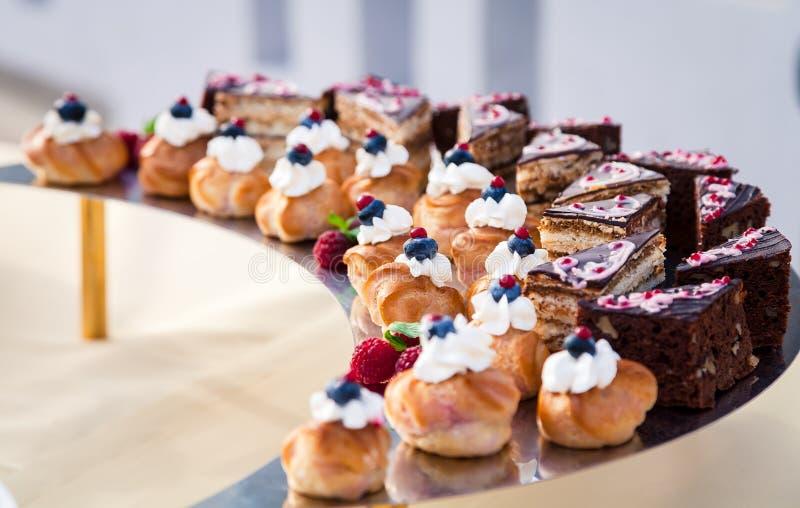 Ljusbruna kakor för Eclairs som dekoreras med bär royaltyfria foton
