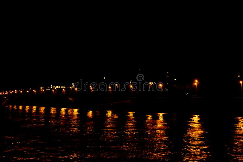 Ljuset av stadslyktor reflekteras i vattnet p? natten Waves p? floden arkivbilder