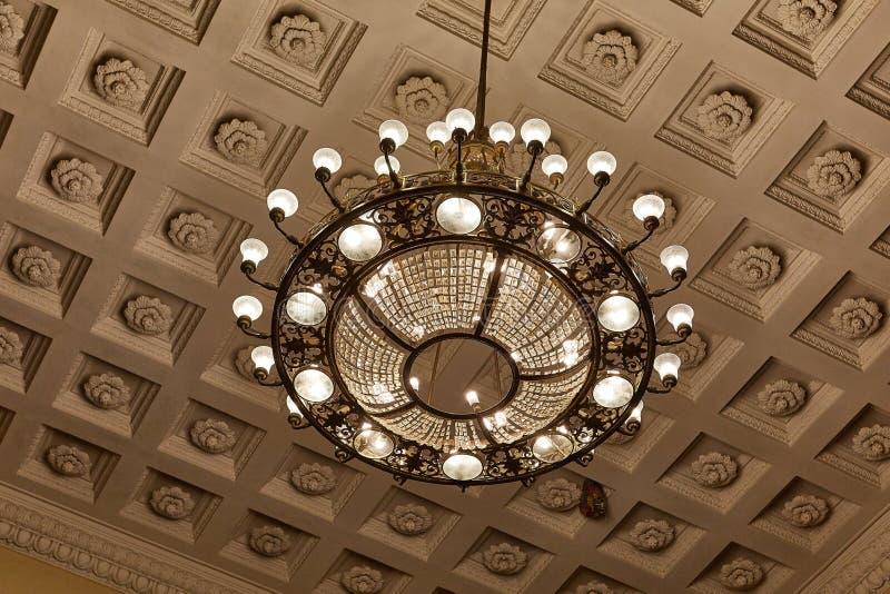 Ljuskrona på decoarted tak royaltyfria bilder