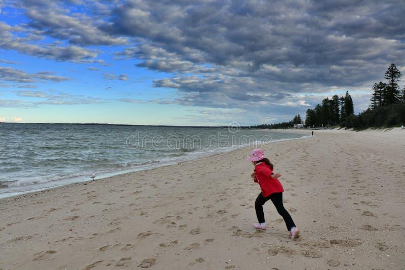 Ljusna Le Sandpappra Strand- som lilla flickan i rött körde till havet fotografering för bildbyråer