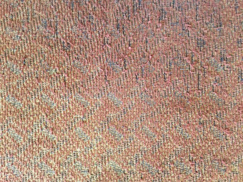 Ljusröd färgbakgrund, texturen av tyget som täcker den gamla stolen royaltyfri bild