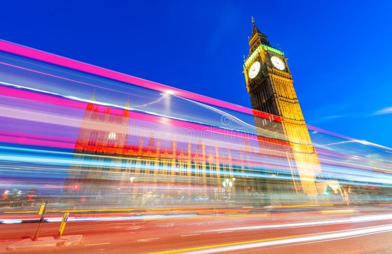 Ljusslingor av den röda bussen framme av Big Ben och Westminster Pala arkivfoto