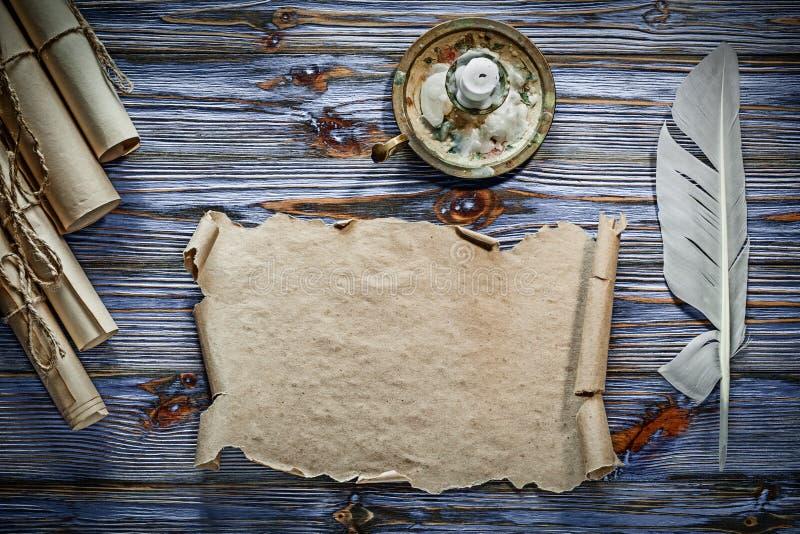 Ljusstake för fjäder för rullande papper för tappning på blå träbackgrou royaltyfri fotografi