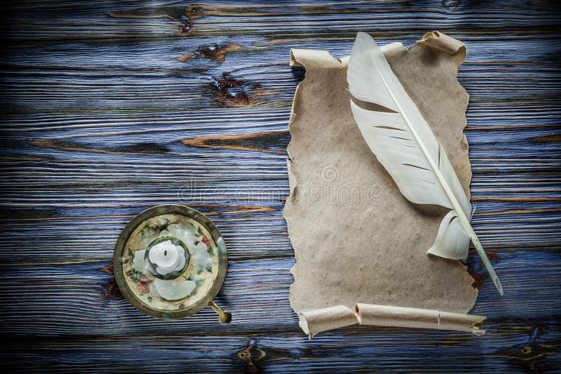 Ljusstake för vingpenna för tappningpapperssnirkel på blå träbakgrund royaltyfria foton