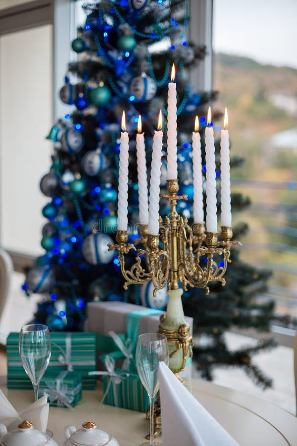 Ljusstake med tända stearinljus på en julgran med gåvor arkivfoto