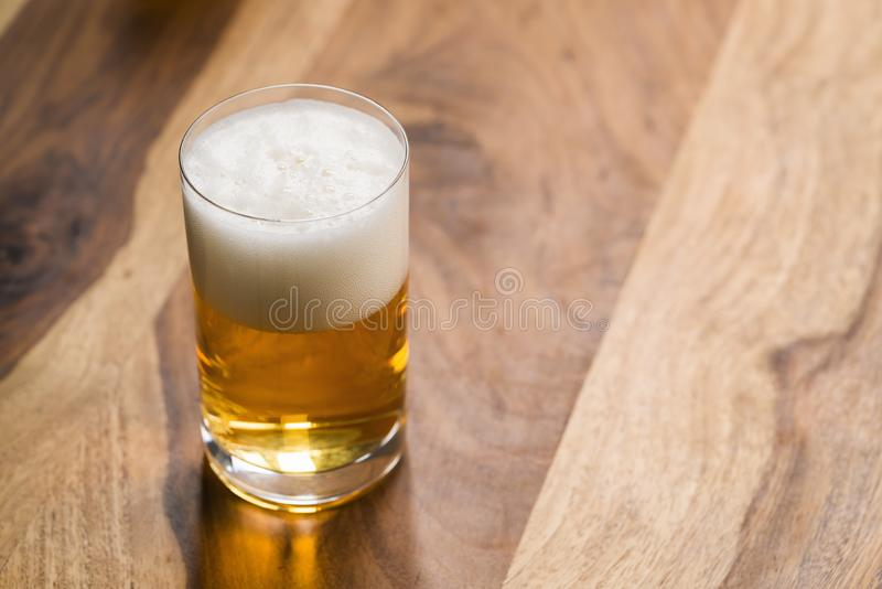 Ljust öl i exponeringsglas på träbakgrund med kopieringsutrymme royaltyfria bilder