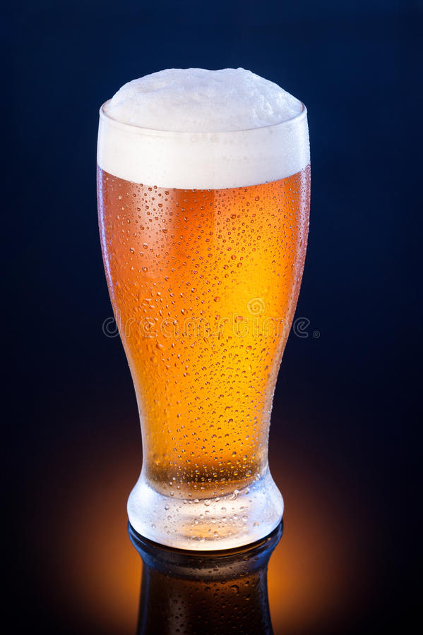 ljust öl i frostigt exponeringsglas över mörker - blå bakgrund royaltyfria bilder