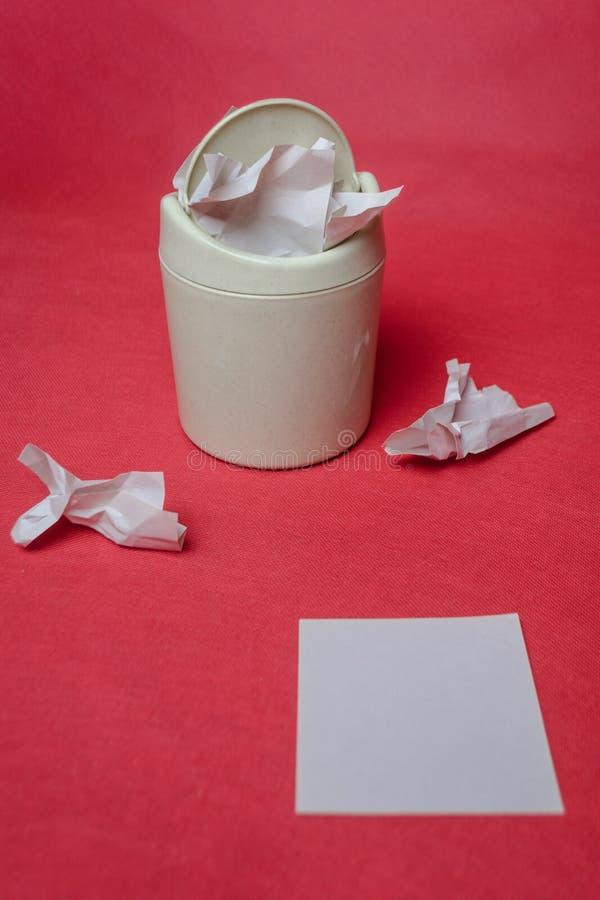 Ljust avfallfack p? en r?d bakgrund Closeup av skrynkliga ark av papper vitt ark av papper f?r text royaltyfri fotografi