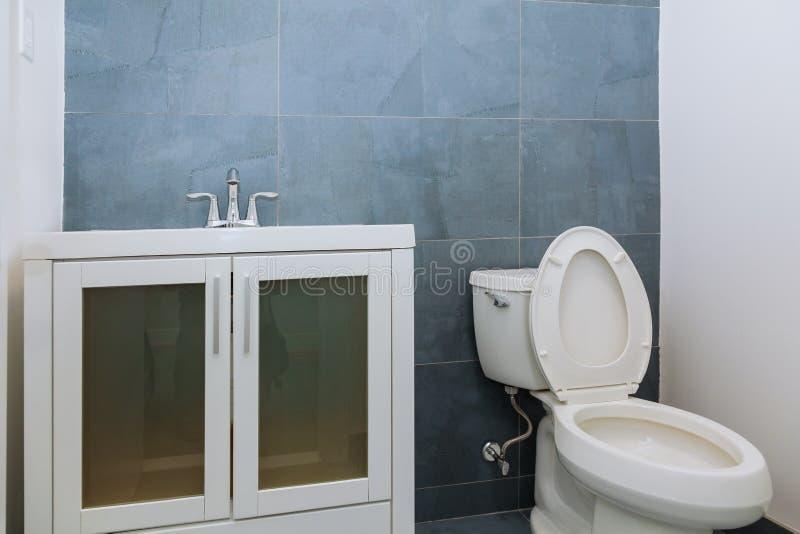 Ljust badrum med strukturella tegelplattor och träfåfängakabinettet arkivfoton