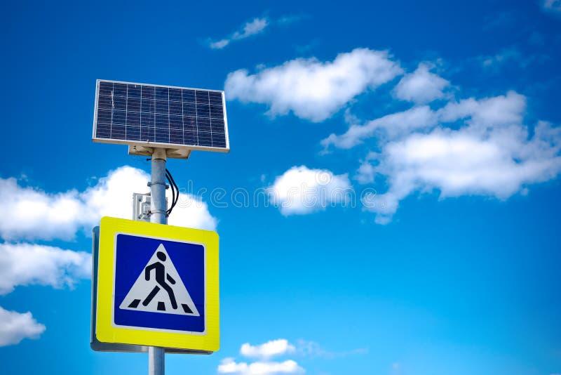 Ljust blått och gult fot- övergångsställetecken med trafikvarning Drivit av sol- energi med dess egen solpanel arkivfoto
