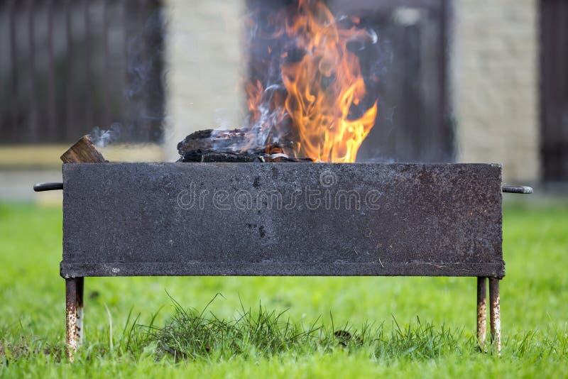 Ljust bränna i metallaskvedträt för grillfest utomhus- Campa, säkerhets- och turismbegrepp arkivbilder