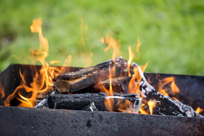 Ljust bränna i metallaskvedträt för grillfest utomhus- Campa, säkerhets- och turismbegrepp arkivfoto