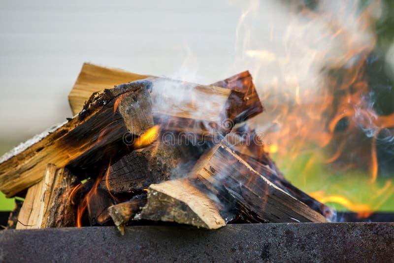Ljust bränna i metallaskvedträt för grillfest utomhus- kam arkivfoton