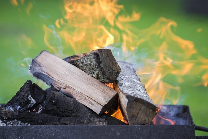Ljust bränna i metallaskvedträt för grillfest utomhus- kam royaltyfria foton