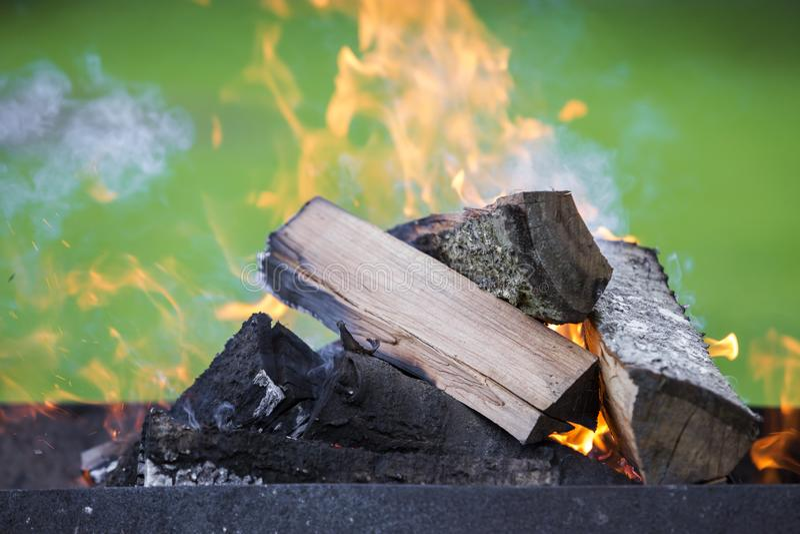 Ljust bränna i metallaskvedträt för grillfest utomhus- kam royaltyfri bild