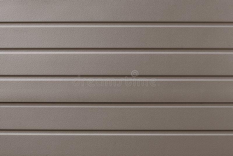Ljust - brun metallisk ribbad yttersida abstrakt modell Beige metallbakgrund Guld- industriell bakgrund av stålplattan Metalline arkivfoton