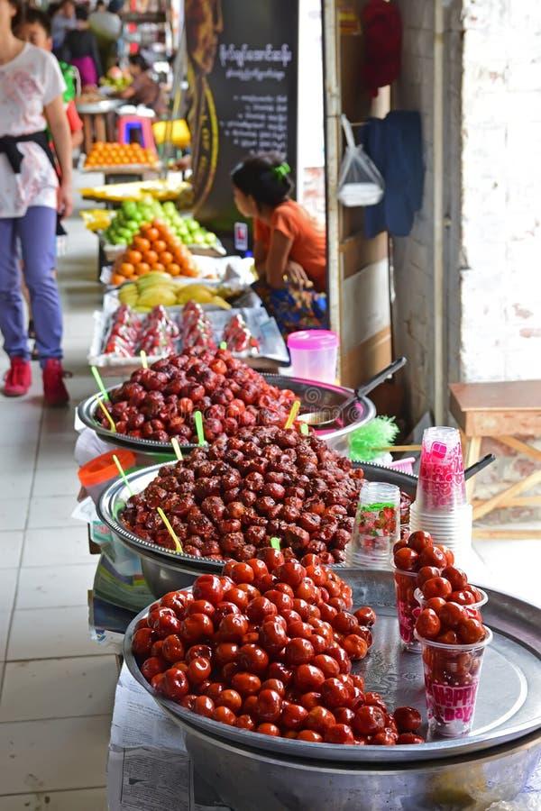 Ljust färgade inlagda kinesiska data som säljs med andra frukter av försäljaren längs den utomhus- korridoren av Bogyoke, marknad royaltyfri fotografi