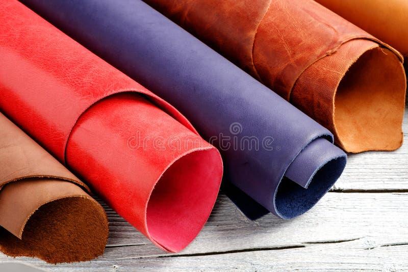Ljust färgat läder i rullar på träbakgrunden Läderhantverk royaltyfri bild