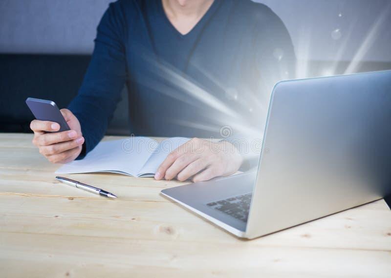 Ljust glöda från anteckningsbokdatoren på träskrivbordet med att använda smartphonen arkivbilder