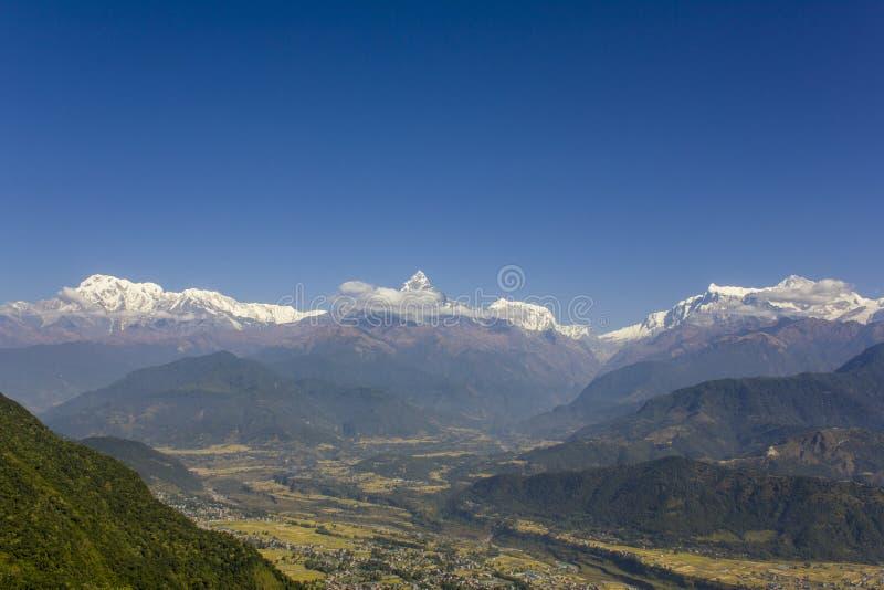 Ljust - grön lutning av en kulle mot bakgrunden av staden i en bergdal och den snöig kanten av Annapurna under en frikänd arkivfoto