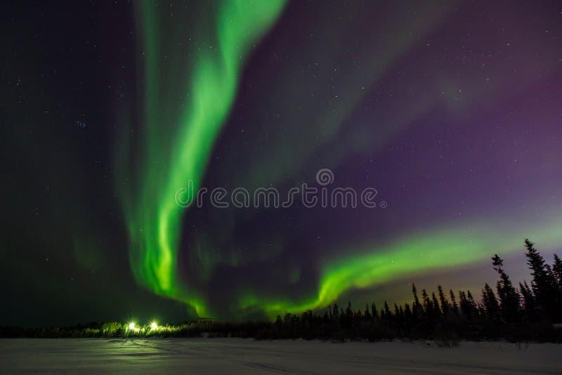 Ljust - gröna exponeringar av nordliga ljus går in i perspektiv utöver svart horisont royaltyfri fotografi