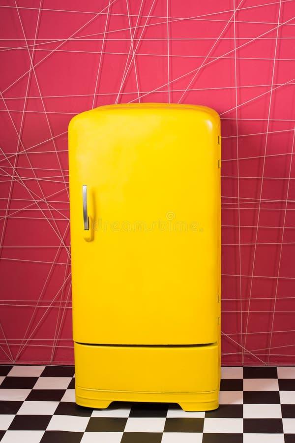 Ljust gult kylskåp i rosa inre Den Retro kylen ser enorm i modern inre Stilfulla inredetaljer royaltyfria foton