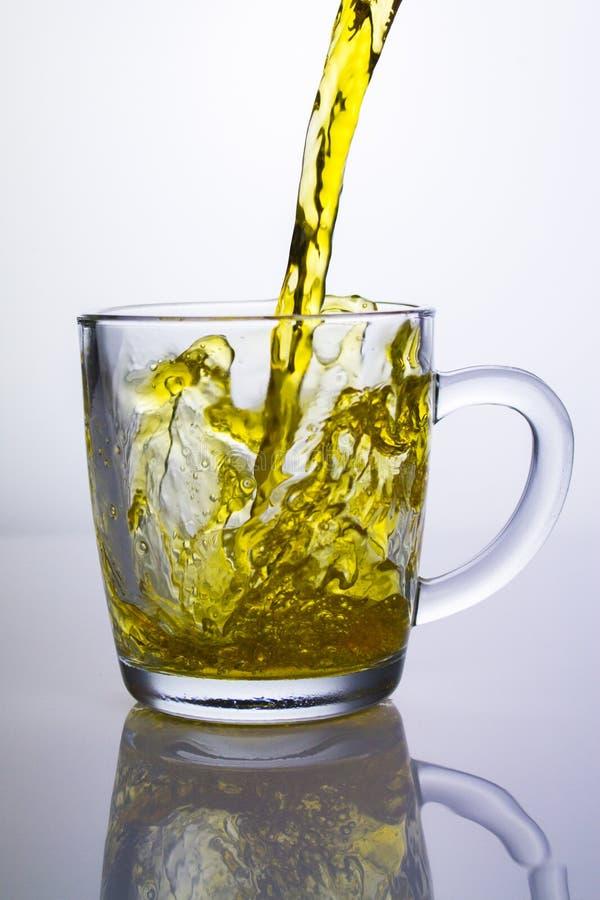 Ljust gult te häller in i ett klart exponeringsglas rånar i en stark stråle på en ljus bakgrund med reflexion royaltyfri fotografi