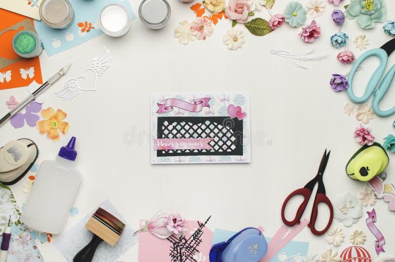 Ljust kort i mitten på en vit bakgrund som omges av kulört papper, pappers- blommor och scrapbooking material arkivfoton