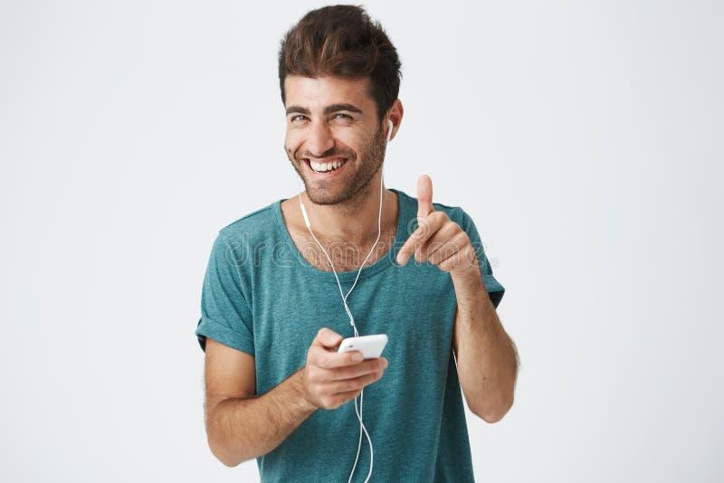 Ljust le den orakade spanska grabben i blå t-skjorta, hållande smartphone, lyssnande musik med hörlurar som skrattar och royaltyfri bild