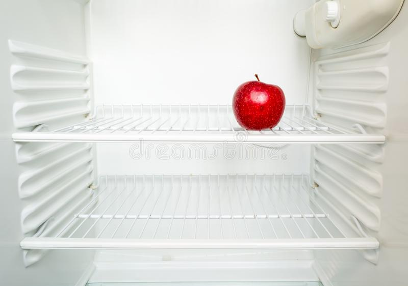 Ljust nytt rött äpple på hylla av det öppna tomma kylskåpet Viktf?rlust bantar begrepp arkivfoton