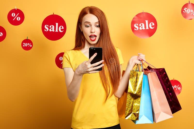 Ljust rödbrun flicka i den stilfulla T-tröja som rymmer adn för shoppingpåsar som gör en påringning fotografering för bildbyråer