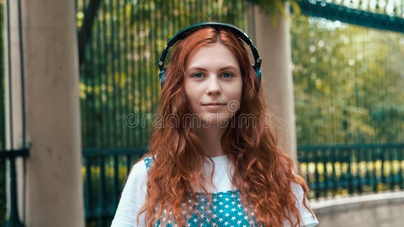 Ljust rödbrun flicka som lyssnar till utomhus- audiobook royaltyfria foton