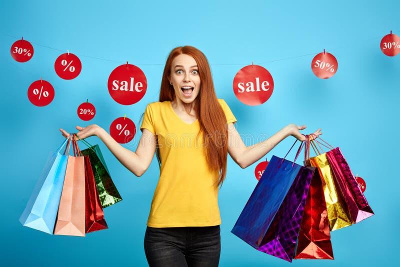 Ljust rödbrun flicka som uttrycker positiv sinnesrörelse, bärande shoppingpåsar royaltyfri bild