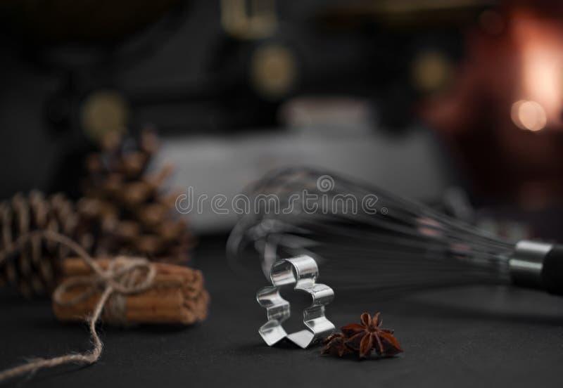 Ljust rödbrun form för brödmanbakning, anisstjärna, kanelbruna pinnar på svart backround royaltyfria foton