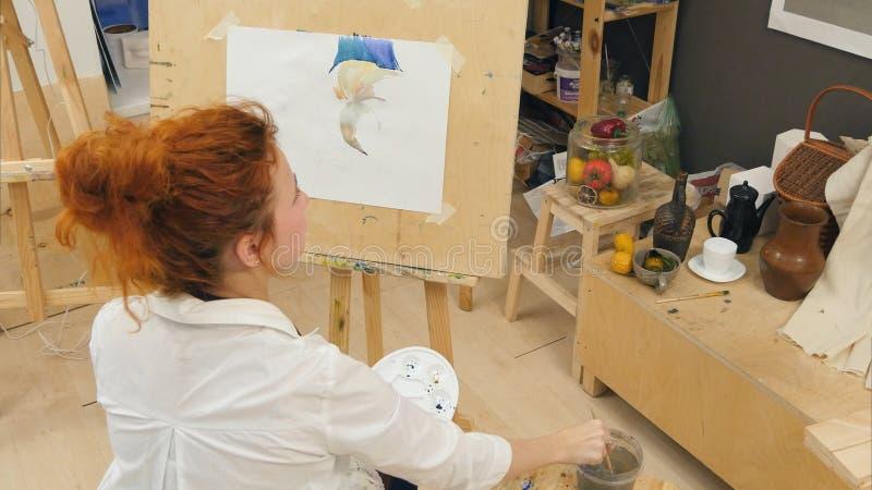 Ljust rödbrun kvinnlig konstnär som använder aquarellen för att måla stilleben arkivbild