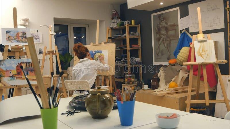 Ljust rödbrun kvinnlig konstnärmålningstilleben i konststudio royaltyfri foto